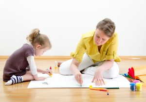 Young woman and little girl drawing together when water underfloor heating has been installed